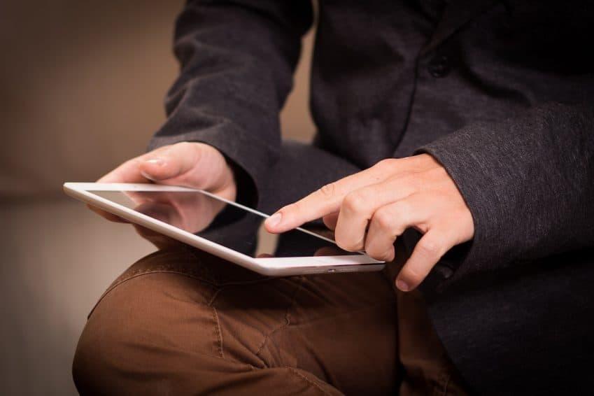 Imagem mostra tablet em close e uma mão mexendo nele.