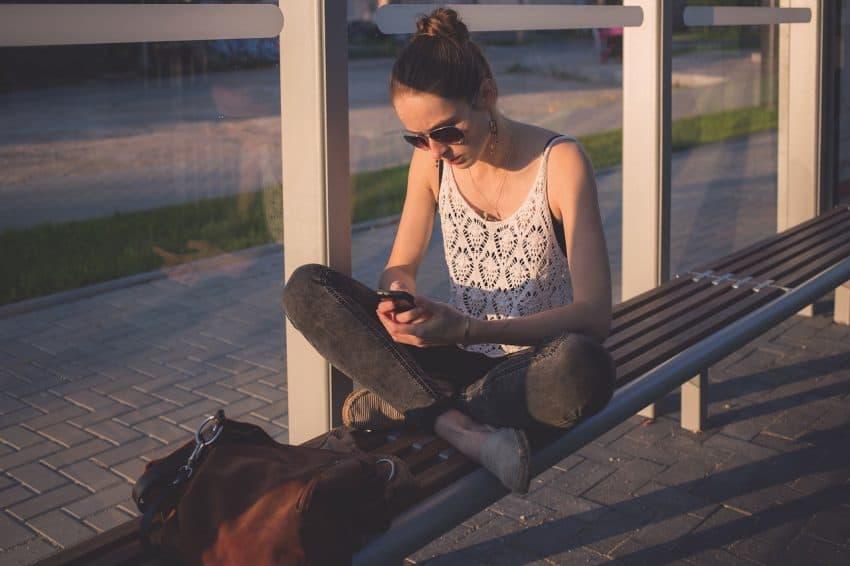 Imagem mostra menina sentada no ponto de ônibus mexendo no celular, usando uma alpargata.