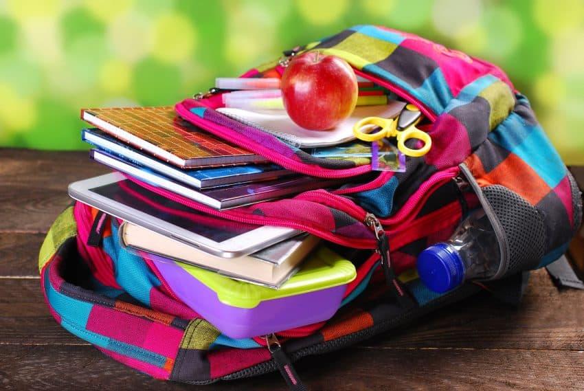Imagem mostra mochila infantil colorida aberta com material escolar dentro.