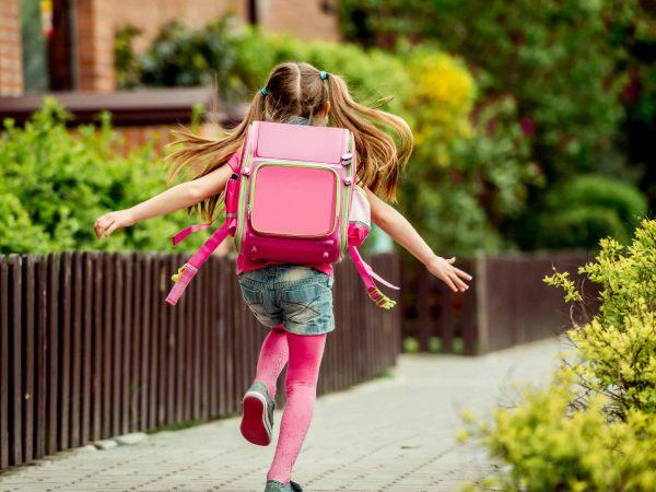 Imagem mostra menina com mochila infantil rosa correndo.
