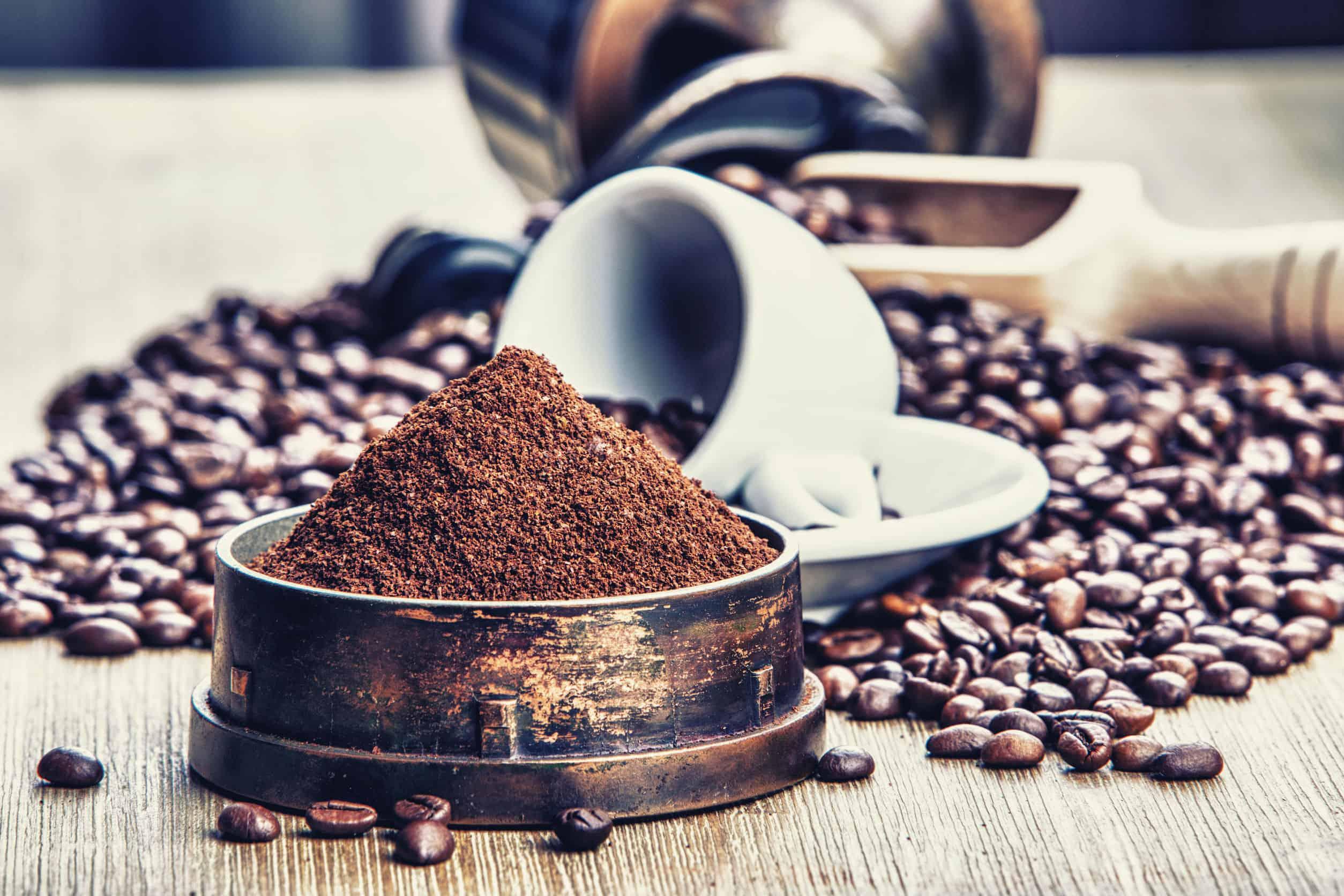 Imagem mostra grãos de café em uma mesa. À frente, pó de café moído.
