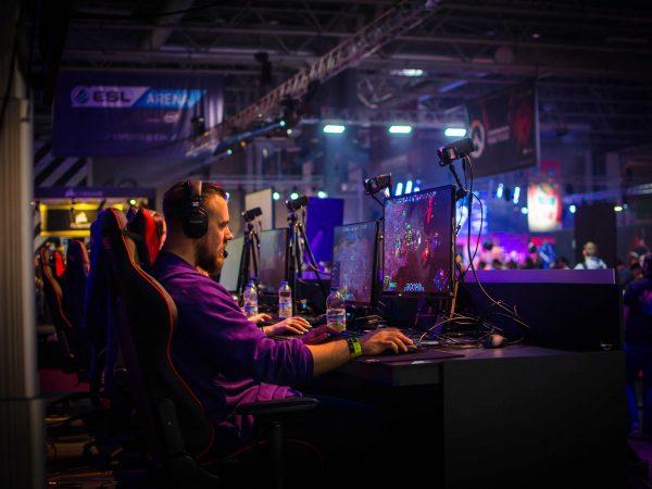 Na foto um homem jogando em um computador usando um headset.