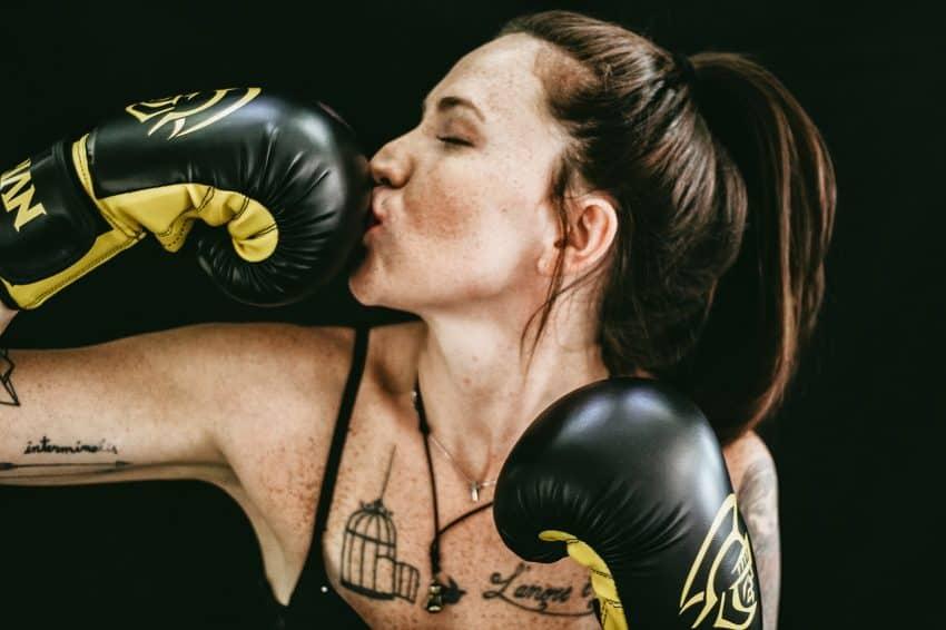 Imagem mostra mulher de olhos fechados beijando sua luva de boxe preta e amarela.