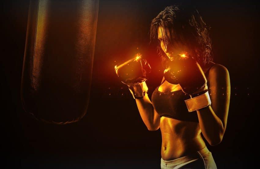 Imagem mostra mulher com luvas de boxe em frente a um saco de boxe, com efeitos luminosos nas luvas.