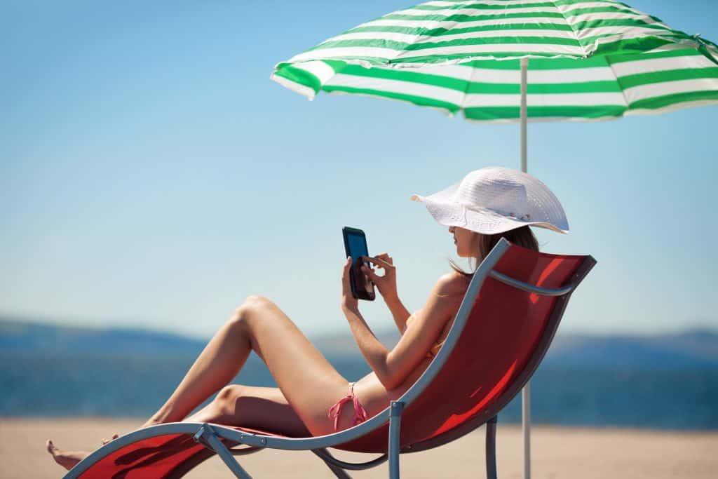 mulher sentada em uma cadeira de praia vermelha mexendo no celular