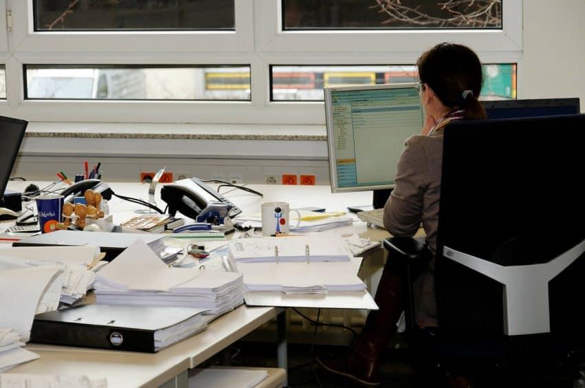 Imagem mostra mulher em frente ao computador. Na mesa, muitos papéis.