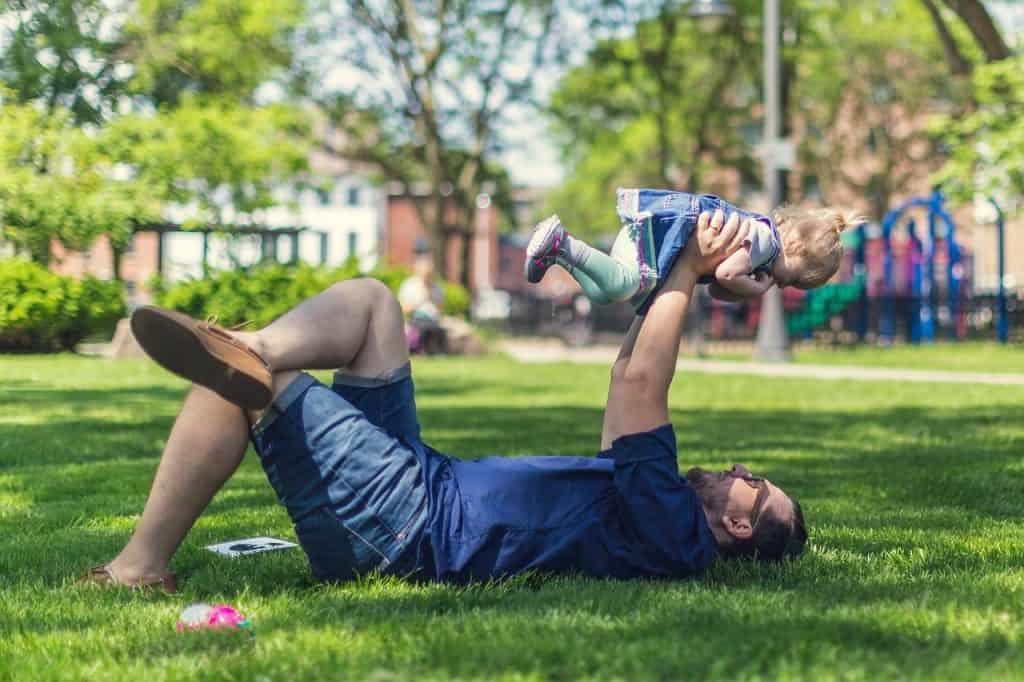 pai brincando com filho na grama