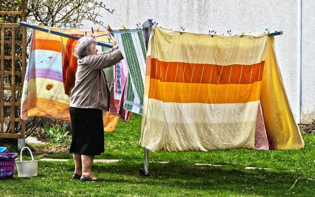 senhora pendurando lençois no varal