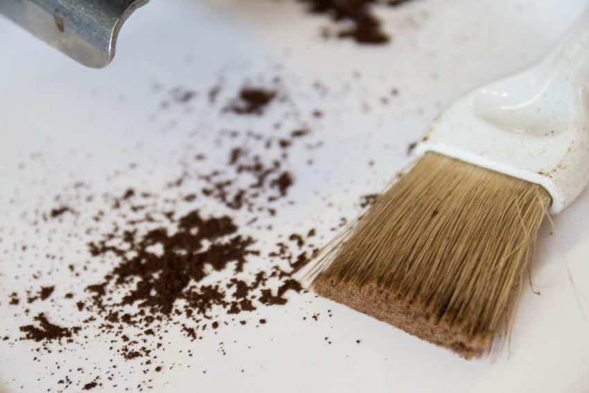 Imagem mostra restos de pó de café em uma mesa ao lado de um pincel de limpeza.