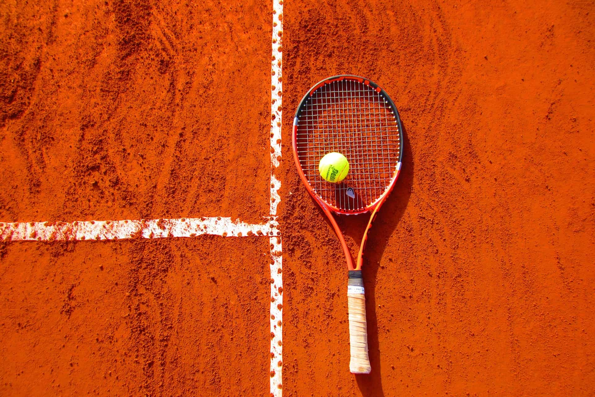 Imagem de uma quadra de tênis de saibro com uma raquete e uma bolinha em cima dela.