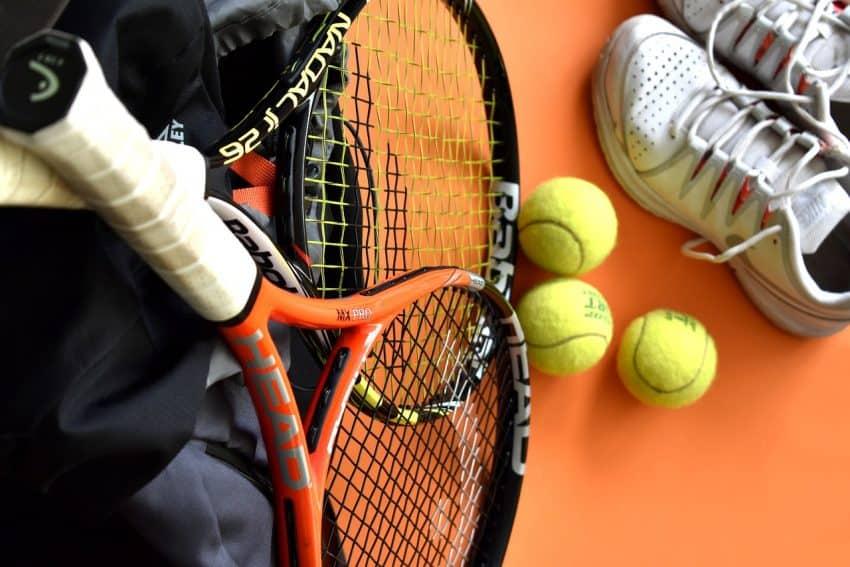 Imagem mostra duas raquetes de tênis, três bolinhas e um par de calçados.