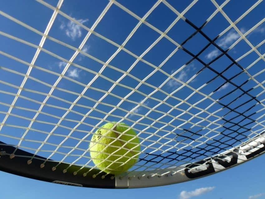 Imagem mostra uma raquete de tênis com uma bola de tênis.