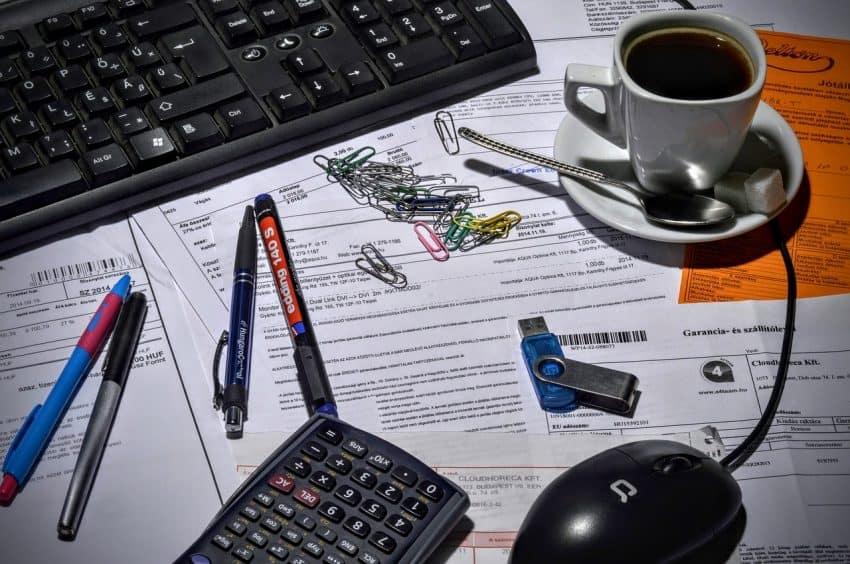 Imagem mostra uma calculadora, um teclado de computador, algumas canetas, um mouse, um café, alguns clips, um pen drive, e tudo isto está sobre alguns documentos.