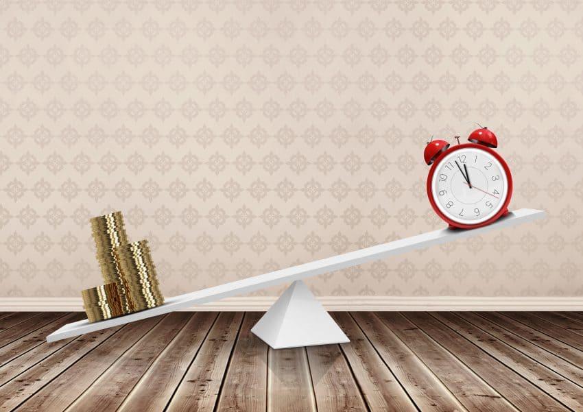 Imagem mostra um relógio e moedas douradas em uma balança.