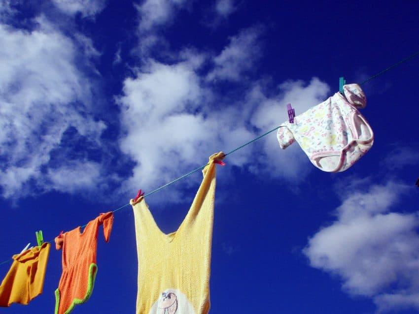 Imagem mostra varal ao ar livre com roupas penduradas e céu azul.