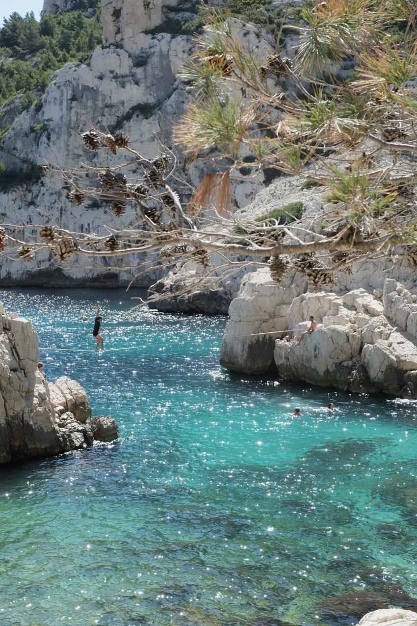 Imagem mostra praticante de slackline se equilibrando na fita de uma margem do rio até outra. Várias pessoas o observam dentro da água ou em cima das rochas.