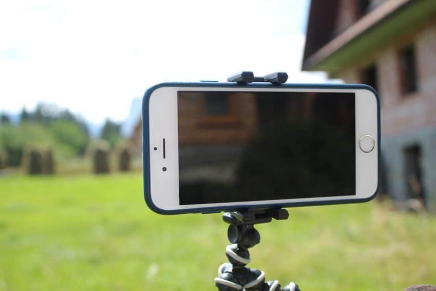 Imagem mostra um celular em um tripé articulado.