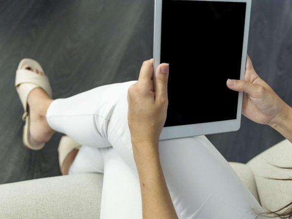 Imagem de uma mulher segurando um tablet com chip.