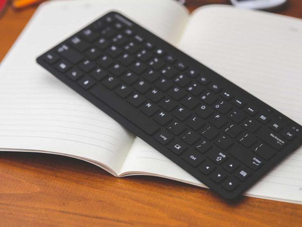 Imagem mostra um teclado sem fio sobre um caderno.