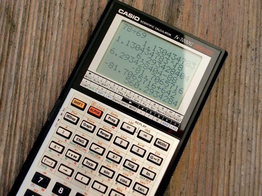 Imagem mostra uma calculadora científica e seu visor com muitos números.