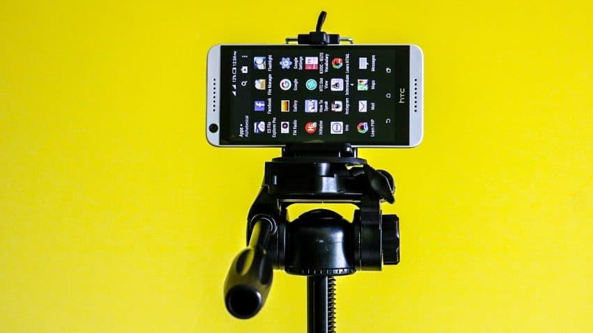 Imagem mostra um celular sobre um tripé contra um fundo amarelo.