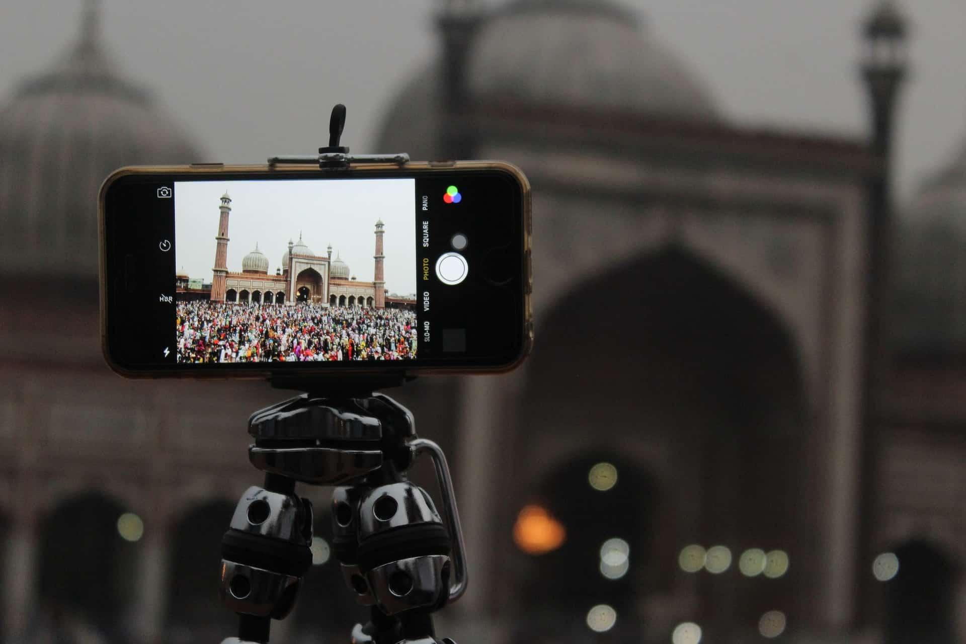 Imagem mostra celular montado em tripé tirando foto de um monumento.