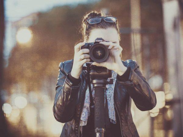 Imagem mostra uma pessoa segurando uma máquina fotográfica com um tripé.