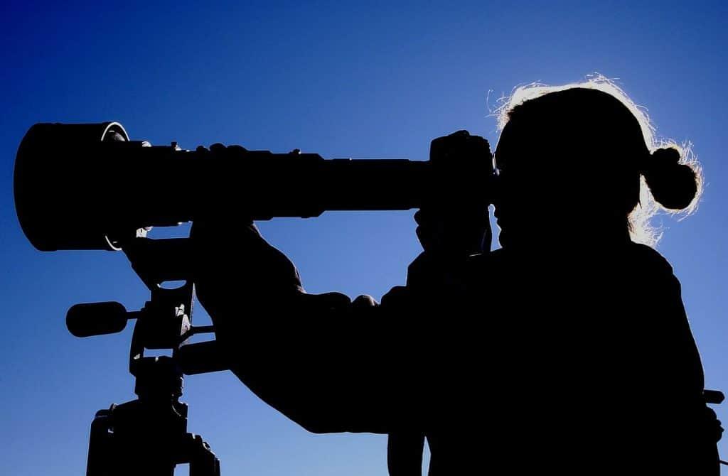 silhueta de mulher fotografando com câmera profissional e tripé