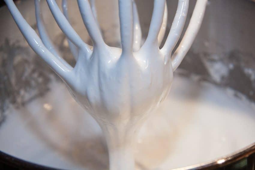 Imagem apresenta um líquido branco, claras em neve, feitas com batedeira de mão.