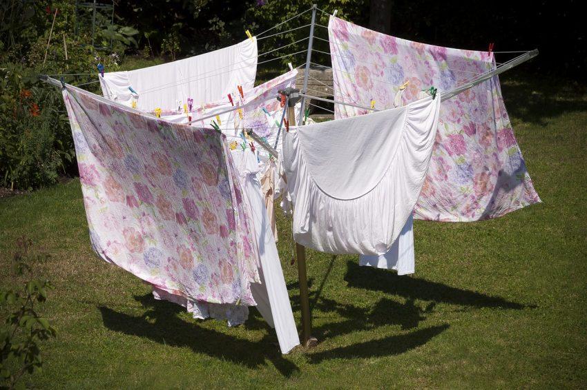 Imagem mostra um varal giratório, com roupas de cama penduradas.