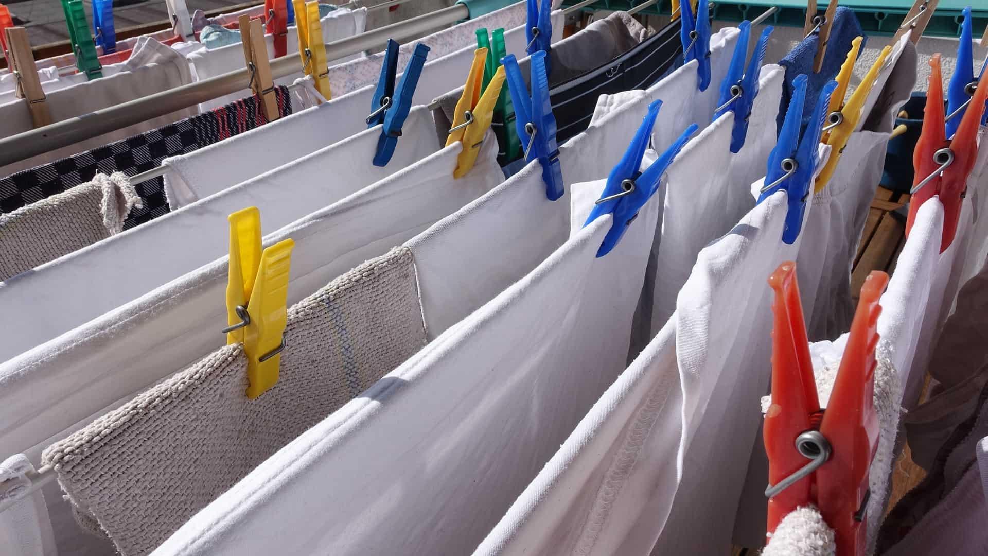Imagem mostra um varal com várias peças de roupa penduradas com grampos.