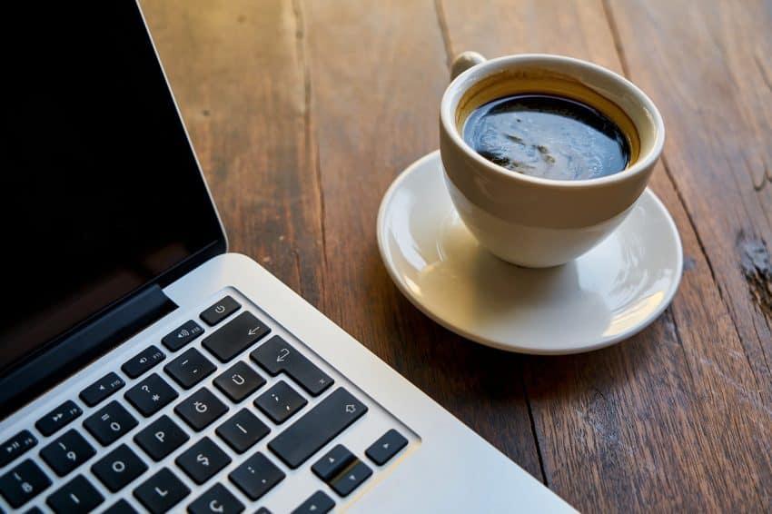 Imagem mostra xícara de café expresso ao lado de computador.