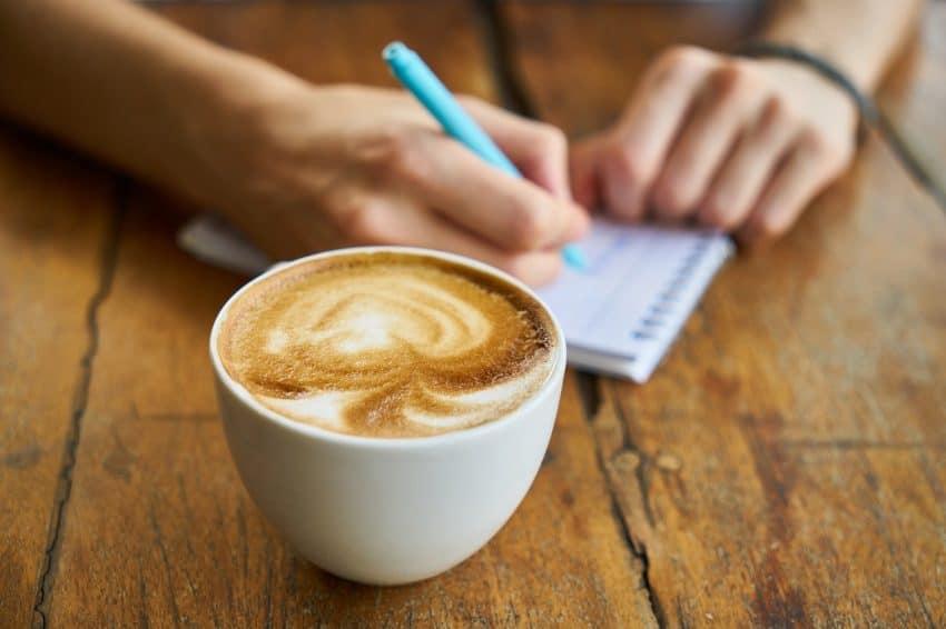 Imagem mostra café na xícara em foco na frente, com pessoa desfocada escrevendo em um caderno atrás.