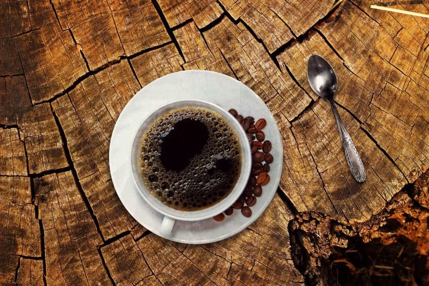 Imagem mostra xícara de café vista de cima com grãos no prato.