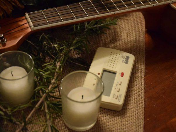 Imagem de um afinador junto à duas velas e um violão.