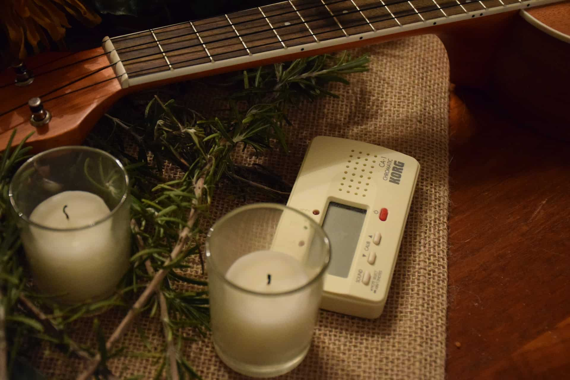 Image of a tuner with two candles and a guitar.