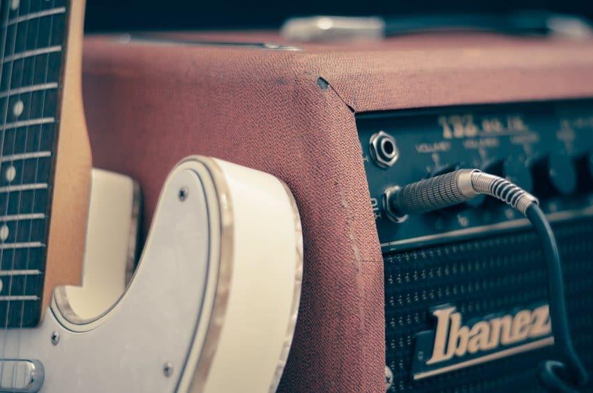 Imagem de um amplificador rosa Ibanez com uma guitarra ao fundo.