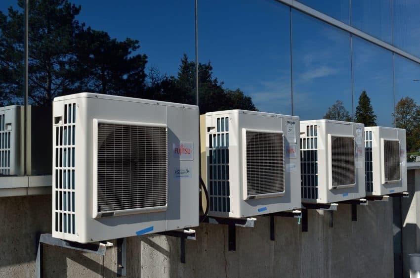 Imagem mostra quatro ares condicionados na parte de fora de um edifício.