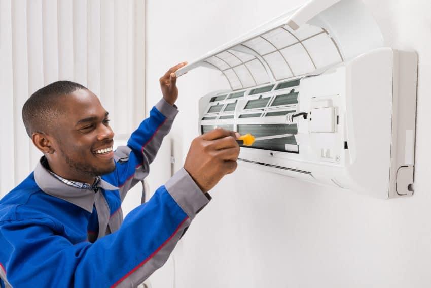 Técnico de ar condicionado fazendo manutenção do aparelho instalado na parede