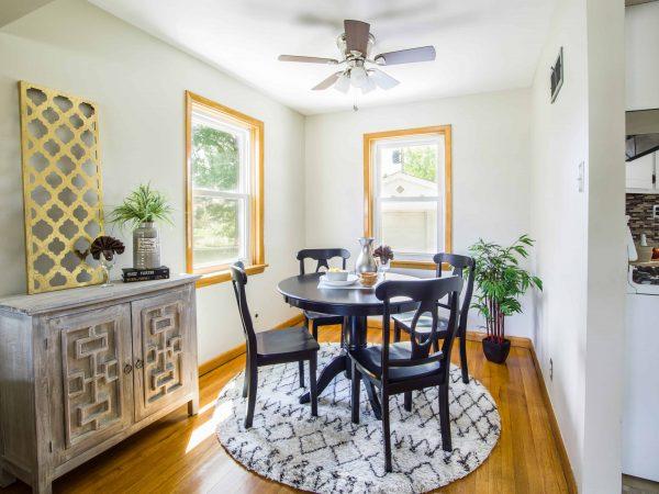 Na foto há uma sala de jantar de piso de madeira com uma mesa e quatro cadeiras na cor preta, ao lado está um armário de duas portas com enfeites em cima.