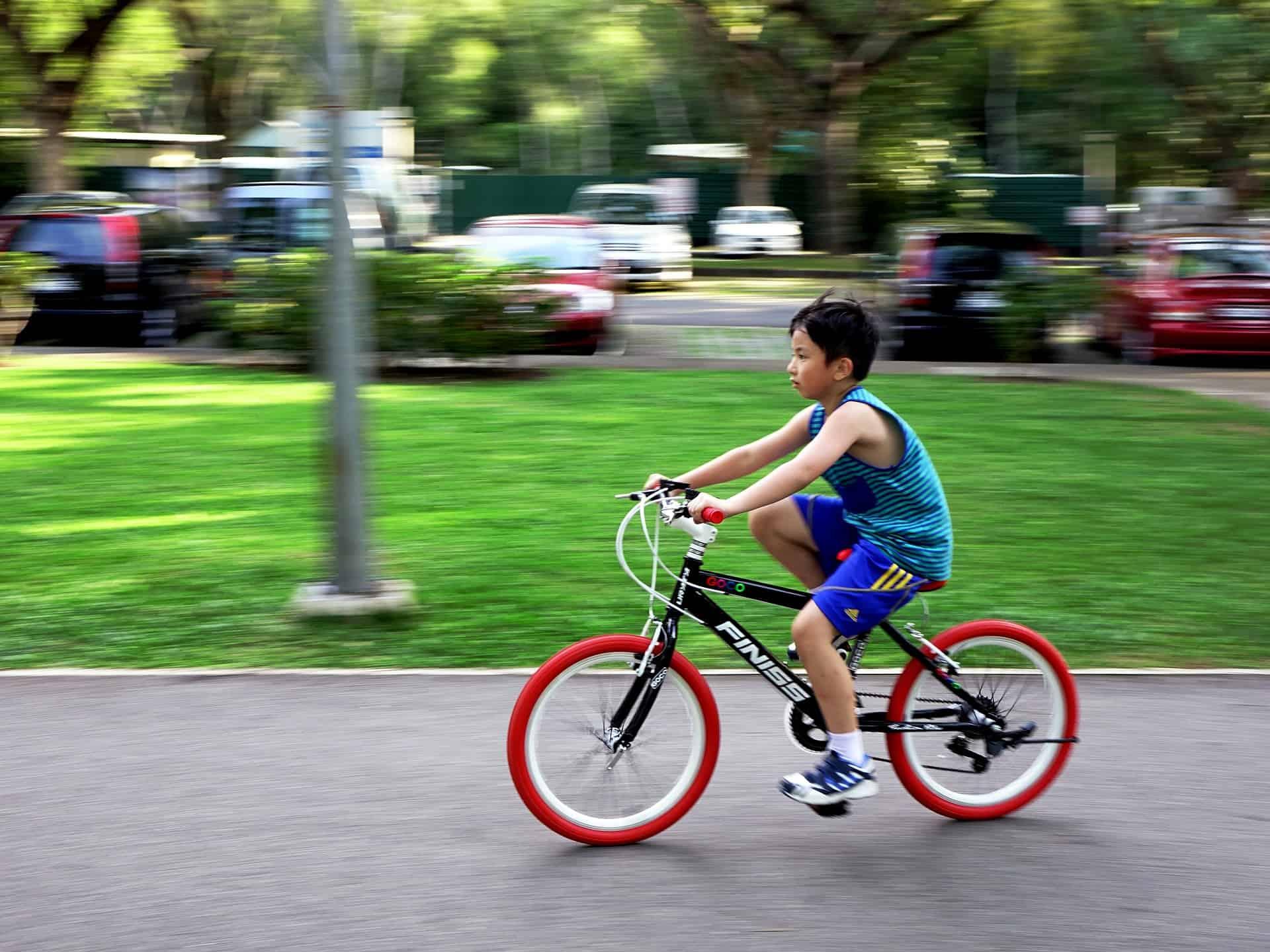 Menino pedalando na cidade com sua bicicleta aro 20.