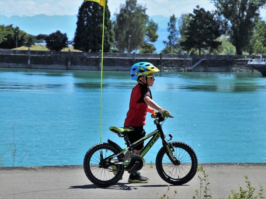 Imagem mostra criança com capacete e andando ao lado de uma bicicleta.
