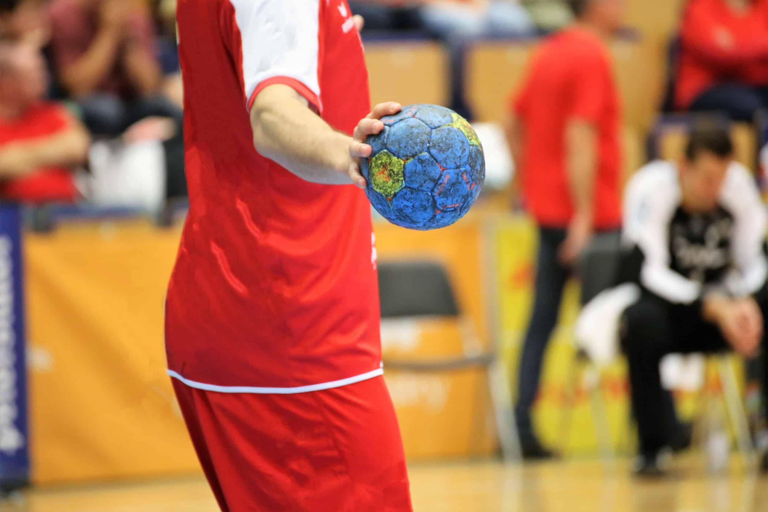 Imagem de um jogador segurando uma bola de handebol. A imagem não mostra sua cabeça.