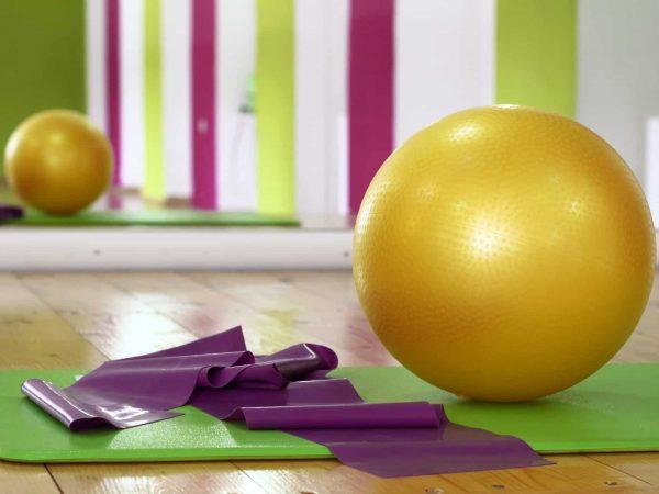 Imagem de bola de pilates sobre esteira de exercício.