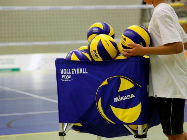 Imagem mostra rapaz depositando bola de vôlei junto a outras em um cesto próximo a uma quadra.