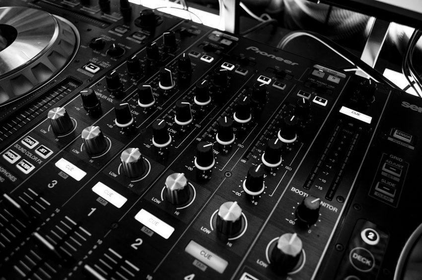 Close de uma mesa de som e seus controles.