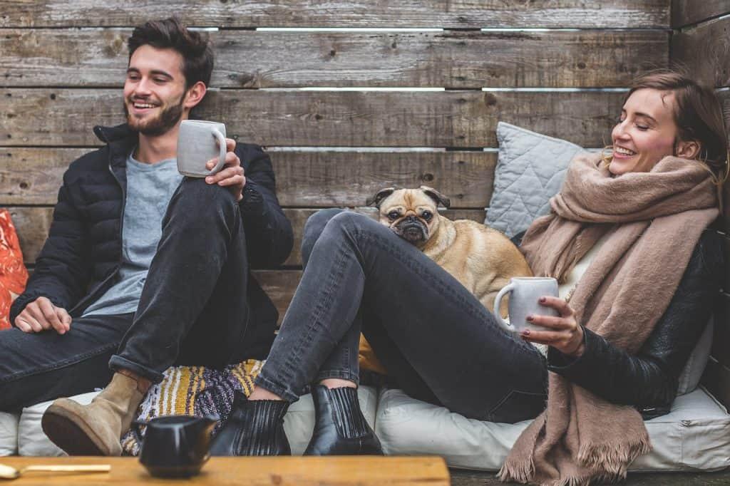 homem e mulher tomando café sentados, sorrindo, ao lado de um cachorro