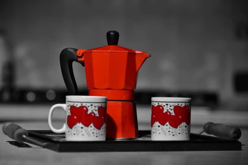 Cafeteira italiana bialetti vermelha com duas xícaras.