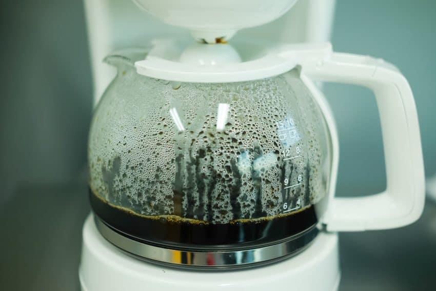 close da jarra de vidro de uma cafeteira elétrica branca com café