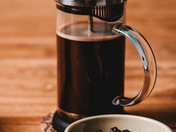Imagem de cafeteira francesa sob mesa de madeira, com grãos de café ao lado.